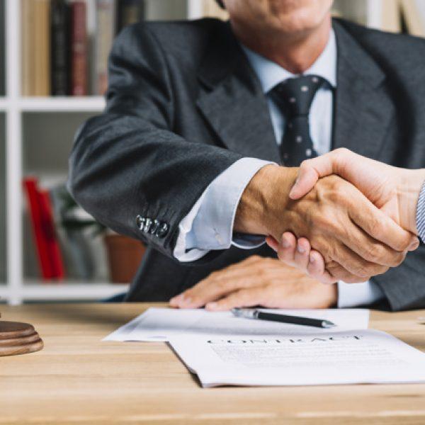 abogado-su-cliente-estrechandose-mano-sobre-escritorio_23-2147898427